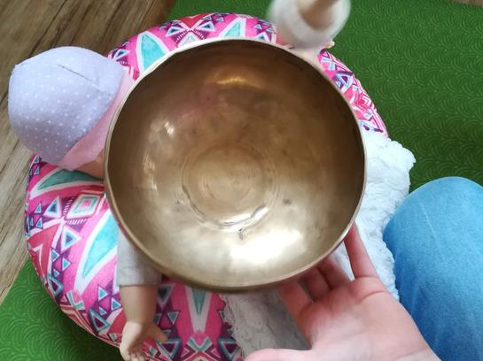 Klangmassage mit Puppe auf dem Rücken